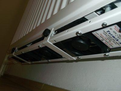 Ventilátor pod radiátor upevnený na panelový radiátor na jeho spodnej strane